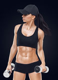 Fitness sporty woman in training pumping up muscles with dumbbells Stock Photos