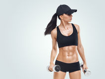 Fitness sporty woman in training pumping up muscles with dumbbells royalty free stock image