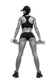 Fitness sporty woman in training pumping up muscles with dumbbells royalty free stock photography