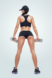 Fitness sporty woman in training pumping up muscles with dumbbells Royalty Free Stock Photos