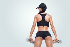 Fitness sporty woman in training pumping up muscles with dumbbells