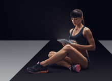 Fitness sporty woman using a digital tablet Royalty Free Stock Photography