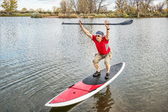 Fitness on stand up paddleboard. Senior male paddler stretching and warming up on a paddleboard before paddling workout on a lake in Colorado royalty free stock image