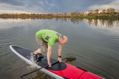 Fitness on stand up paddleboard. Senior male is starting paddling workout on his stand up paddleboard on a lake in Colorado Royalty Free Stock Photo