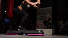 Fitness stap, opleiding, aerobics, sportconcept - Atletische vrouwentrainer bij stap doen aëroob met steppers binnen stock video