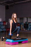 Fitness step, training, aerobics, sport concept - Athletic woman trainer at step doing aerobic with steppers indoors Royalty Free Stock Photos