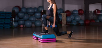 Fitness step, training, aerobics, sport concept - Athletic woman trainer at step doing aerobic with steppers indoors Royalty Free Stock Image