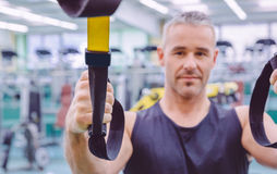 Fitness strap in the hand of man training. Closeup of fitness strap in the hand of man doing hard suspension training in a fitness center. Healthy and sporty Stock Images