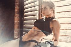 Fitness strength training workout concept - muscular bodybuilder sport girl doing exercises in gym. Fitness strength training workout concept background stock image