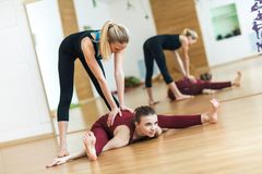 Fitness, stretching practice, yoga teacher with student working out in sports club, instructor helping female student to do asana royalty free stock photos