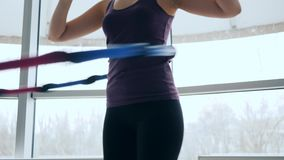 Fitness studio, shapely girl rotates ring at waist in sports center on background of large windows. Fitness studio, shapely girl rotates ring at waist in sports stock footage