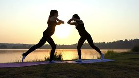 Fitness at sunset near lake - two young and slender girls. The action in the real time stock video