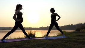 Fitness at sunset near lake - two young and slender girls. The action in the real time stock footage