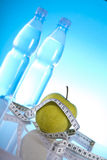 Fitness symbols. Bottles of mineral water and green apple Stock Photos