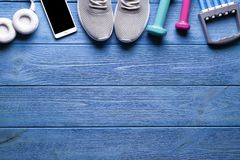 Fitness symbols - dumbbells, sports shoes and smartphone. With headphones on blue wooden background stock photography