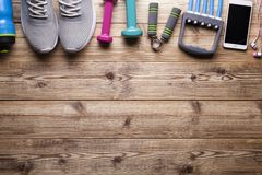 Fitness symbols and equipment - sneakers, water, dumbbell. And smartphone with earphones on wooden background stock images