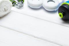 Fitness symbols - water, towel and earphones on wooden planks. Fitness symbols - water, towel and earphones on white wooden planks royalty free stock photography