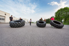 Fitness team flipping heavy tires outdoor Royalty Free Stock Image