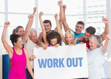 Fitness team standing with placard with work out text in gym. Happy fitness team standing with placard with work out text in gym Royalty Free Stock Images