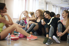 Fitness with team. Women resting on the floor of gymnasium Royalty Free Stock Photography