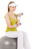 Fitness teenager woman with dumbbell sit on ball Royalty Free Stock Image