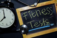 Fitness Tests handwriting on chalkboard on top view. The words Fitness Tests handwriting on chalkboard on top view. Alarm clock, stethoscope on black background stock photos