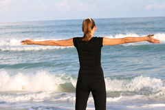 Fitness time. Woman doing fitness exercises on the beach Stock Image