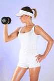 Fitness time. Young woman with dumbbell in white dress Royalty Free Stock Photos