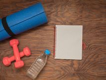 Fitness time, everything is ready for a good workout. Time fitness- water bottle, rug and dumbbells. Ahead of class training Royalty Free Stock Photo