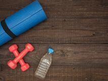 Fitness time, everything is ready for a good workout. Time fitness- water bottle, rug and dumbbells. Ahead of class training Stock Photos