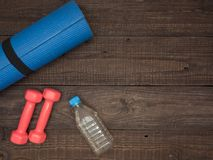 Fitness time, everything is ready for a good workout. Time fitness- water bottle, rug and dumbbells. Ahead of class training Royalty Free Stock Photos