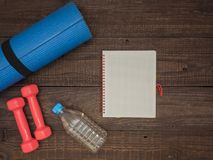 Fitness time, everything is ready for a good workout. Time fitness- water bottle, rug and dumbbells. Ahead of class training Royalty Free Stock Photography