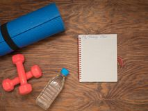 Fitness time, everything is ready for a good workout. Time fitness- water bottle, rug and dumbbells. Ahead of class training Stock Photo