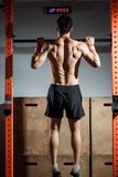 Attractive young male adults doing pull ups on bar in cross fit training gym. Fitness toes to bar man pull-ups bars workout exercise at gym Stock Images