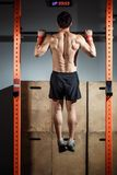 Attractive young male adults doing pull ups on bar in cross fit training gym. Fitness toes to bar man pull-ups bars workout exercise at gym Royalty Free Stock Photography