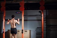 Attractive young male adults doing pull ups on bar in cross fit training gym. Fitness toes to bar man pull-ups bars workout exercise at gym Stock Photos