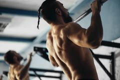 Two Fitness toes to bar men pull-ups tree bars workout exercise at gym. Fitness toes to bar men and women pull-ups tree bars workout exercise at gym royalty free stock photography