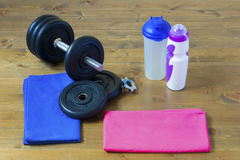 Fitness together family every day. Dumbbells and towel lying on the floor for men and women Royalty Free Stock Photo