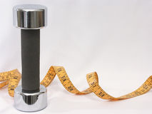 Fitness Tools. Photo of hand weight and measuring tape on white background with room for ad copy Stock Photo