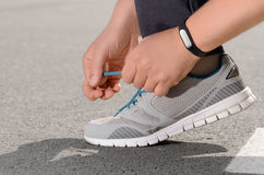 Fitness tracker. Hand wearing fitness tracker tying shoelaces on asphalt road royalty free stock image