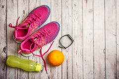 Fitness tracker, orange, water bottle and pink sneakers on light wooden table with copy space. Top view. Fitness tracker, orange, water bottle and pink sneakers stock photo