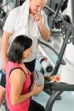 Fitness trainer adjust machine active man exercise Stock Photo