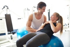 Fitness Trainer Assisting a Woman on Exercise Ball Stock Image