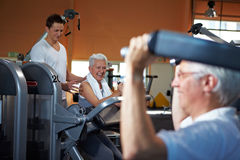 Fitness trainer coaching senior. Fitness trainer coaching two senior people in a gym Stock Photo