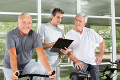 Fitness trainer coaching senior. Fitness trainer with clipboard coaching happy senior people in gym Royalty Free Stock Photos