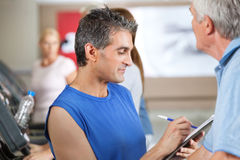 Fitness trainer coaching senior on. Treadmill in gym Royalty Free Stock Photography