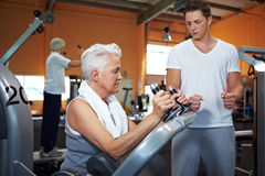 Fitness trainer coaching woman. Fitness trainer coaching two senior people in a gym Royalty Free Stock Images