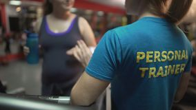Fitness trainer consulting overweight lady exercising in gym, weightloss control. Stock footage stock video footage