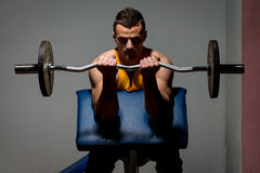 Fitness trainer doing heavy weight exercise for biceps Stock Photo
