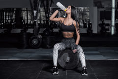 Fitness trainer drinks water from a bottle. Royalty Free Stock Images